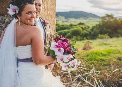 a groom and his wife holding a bouquet of pink and white flowers