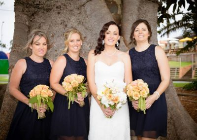a bride and her maids each holding a bouquet of white and yellow roses