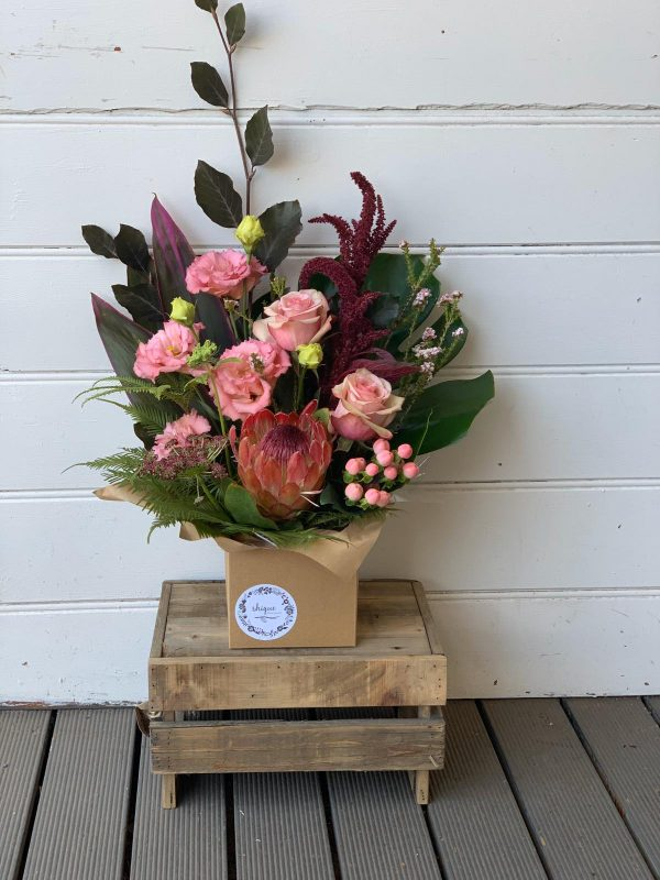 flower arrangement in a box on a wooden stand