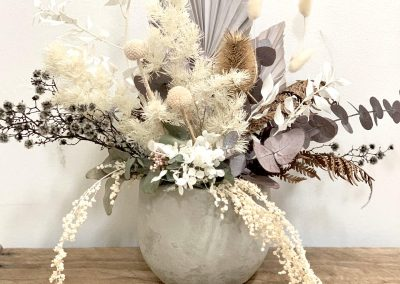 an arrangement of dried flowers in a ceramic pot