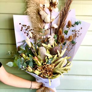a lady holding an arrangement of dried flowers