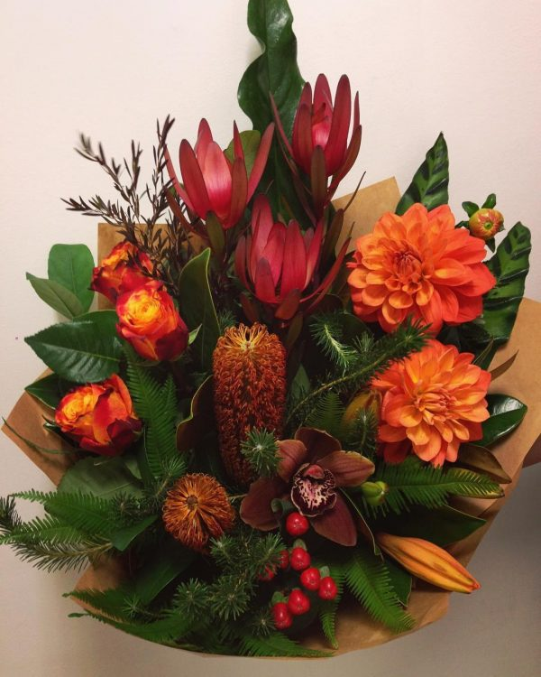 a bouquet of red and orange flowers with green leaves