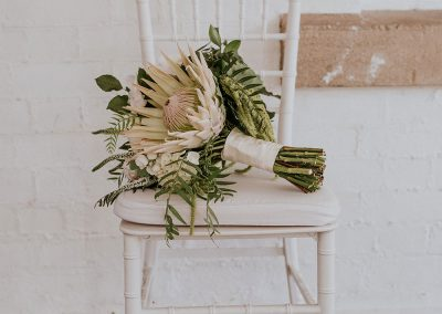 a bouquet of white and green flowers and trimmings on a white chair