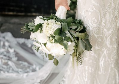 a bride holding a bouquet of white and green flowers and trimmings