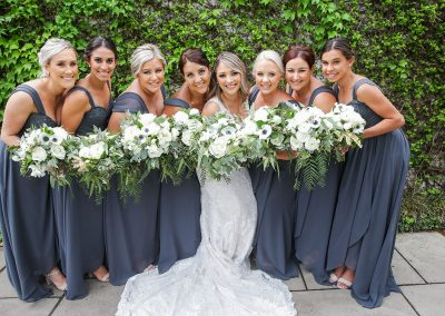 a bride and her maids each holding a bouquet of white flowers