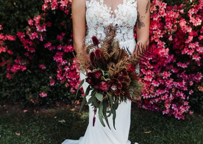 a bride holding a bouquet of red and brown flowers and trimmings