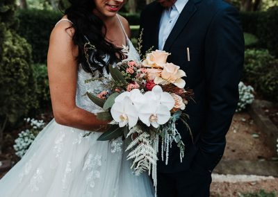 groom with his bride holding a bouquet of flowers