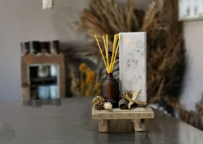 a jar of scented sticks on wood stand